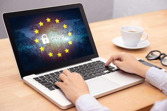 Person typing on laptop with GDPR logo overlaid on world map image