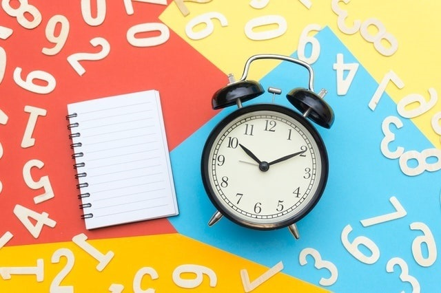 Alarm clock surrounded by multi colored paper and a blank notebook, with white numbers scattered