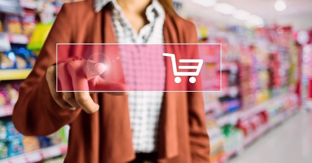 Woman in store pressing digital shopping cart button overlay